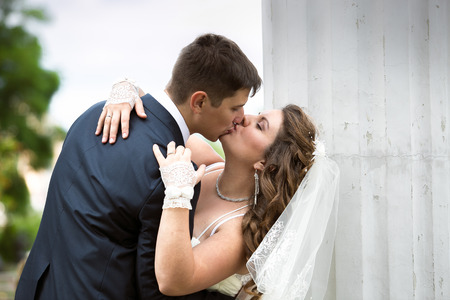 passionately: Closeup portrait of beautiful bride and groom kissing passionately on street Stock Photo