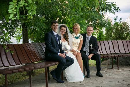 witnesses: Just married couple and two witnesses sitting on bench at park Stock Photo