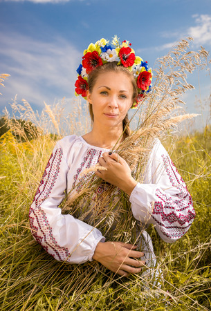 Portrait of beautiful ukrainian woman in embroidered shirt holding sheaf of wheat photo