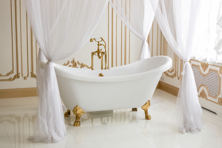 Beautiful view of white luxurious bath with golden legs at bathroom