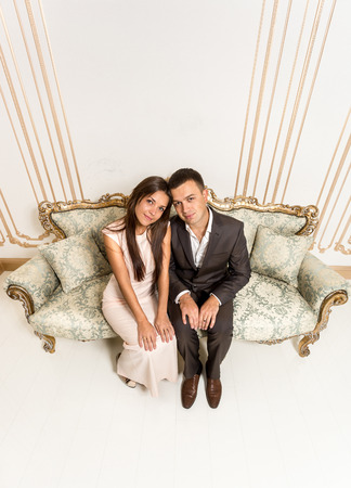 luxurious sofa: Wide angle portrait from high point of young man and woman sitting on luxurious sofa at room Stock Photo