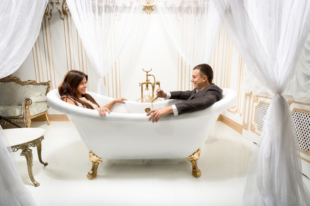 Young clothed man and woman having fun in luxurious bath