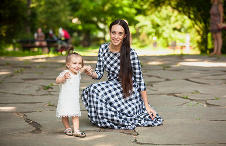 Beautiful woman having fun with baby daughter at park photo