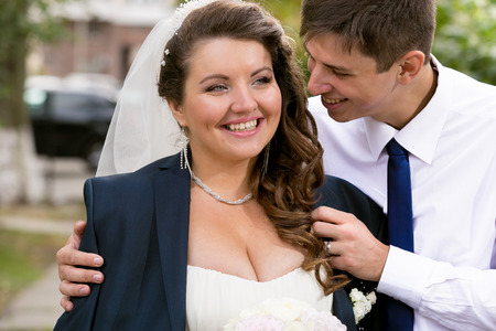 Closeup portrait of handsome groom hugging chubby bride from back Stock Photo