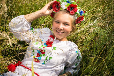 Portrait of smiling ukrainian girl in national clothes lying on field photo