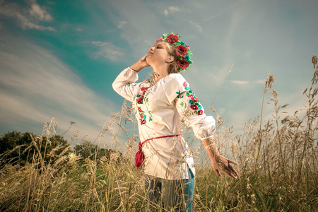 Portrait of beautiful woman in ukrainian clothes at field at windy day photo