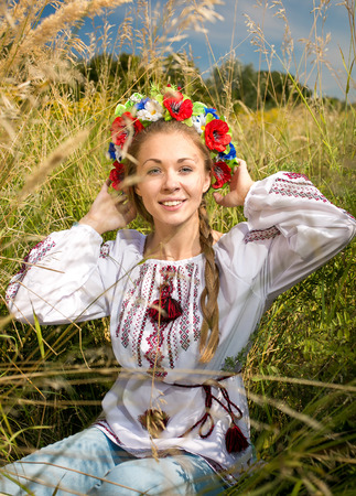 Beautiful ukrainian girl in national clothes sitting on meadow photo