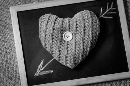 Black and white photo of drawn by chalk arrow going through knitted heart photo