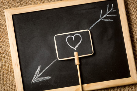 Conceptual photo of heart with arrow drawn by chalk on blackboard photo