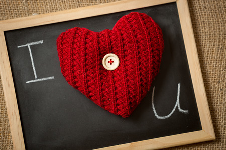 declaration: Closeup photo of declaration of love on blackboard with red knitted heart