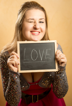 Cute laughing woman posing with word Love written on blackboard photo