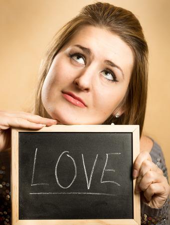 Closeup portrait of thoughtful woman holding word Love written on blackboard photo
