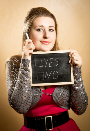 undetermined: Portrait of smiling woman making decision on white chalkboard