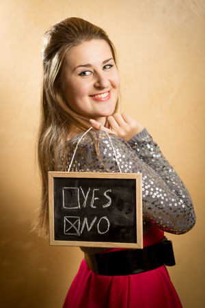 Beautiful smiling woman holding blackboard with two answers photo