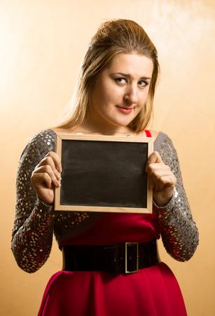 shy woman: Cute shy woman posing with empty blackboard