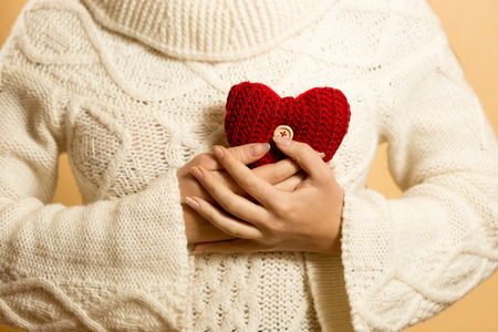 life giving birth: Conceptual photo of woman holding red heart at chest