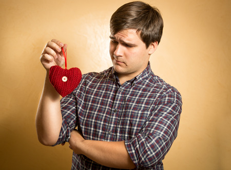 suspiciously: Portrait of handsome man looking suspiciously on decorative red heart