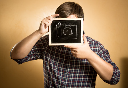 Young hipster man photographing using painted on blackboard camera photo