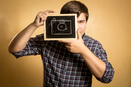 Portrait of handsome young man holding camera drawn on small blackboard photo