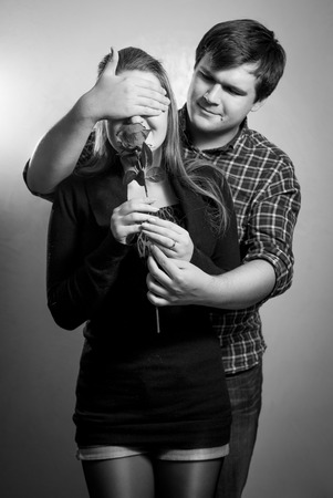 gist: Black and white portrait of young man covering girlfriends eyes for surprise