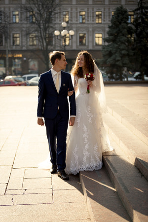 hold hands: Beautiful just married couple walking on street at sunny day Stock Photo