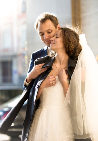 Portrait of caring groom hugging beautiful bride on street at cold day photo