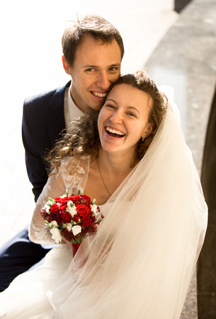 Portrait of happy laughing bride and groom on street at sunny day