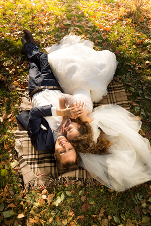 a newly married couple: Beautiful just married couple lying on yellow leaves at park