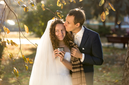 hot drinks: Portrait of happy smiling bride and groom drinking hot tea at autumn park Stock Photo