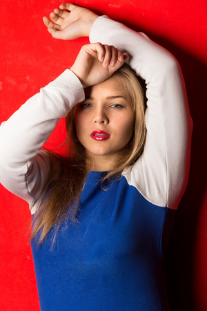 Closeup portrait of sporty blonde woman leaning against red background photo