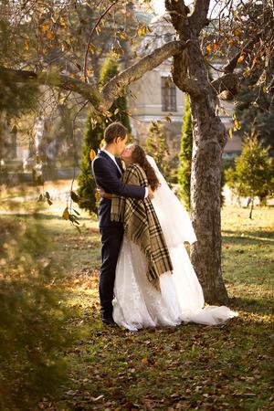 Handsome groom hugging cute bride under tree at autumn park Stock Photo