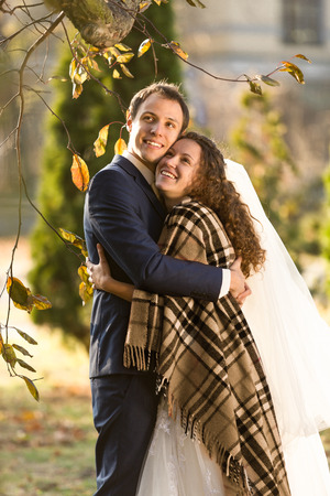 Happy smiling bride and groom hugging under plaid at autumn park photo