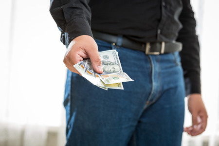 Closeup photo of man in jeans and shirt holding hundred dollar banknotes photo
