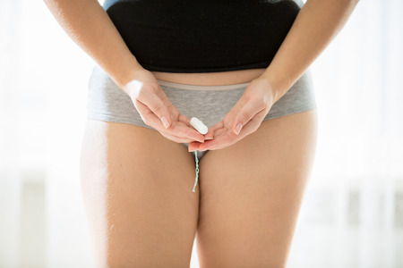 female vagina: Closeup conceptual photo of young woman holding menstrual tampon in hands Stock Photo