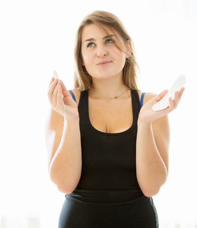 sanitary napkins and tampons: Portrait of cute brunette woman choosing between menstrual pad and tampon