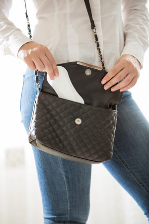 Closeup photo of young stylish woman putting hygiene pad in handbag