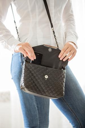 Close-up foto van jonge stijlvolle vrouw die cellphone van handtas
