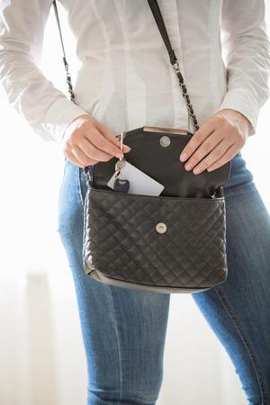 accommodation broker: Closeup portrait of woman taking keys out of purse Stock Photo