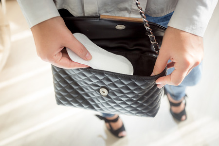 young girl: Closeup photo of young woman putting menstrual pad out of handbag Stock Photo