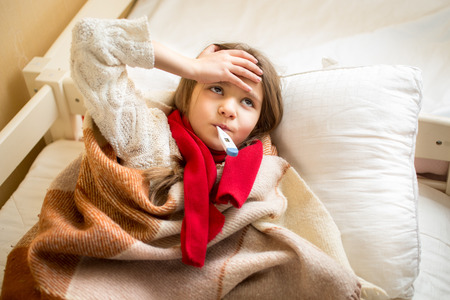 sick person: Portrait of little sick girl measuring temperature and holding hand on head