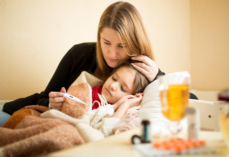 ni�os enfermos: Madre joven que controla temperatura de la hija enferma en la cama Foto de archivo