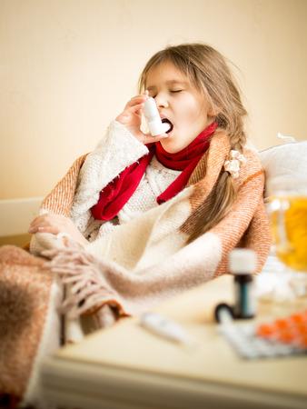 asma: Retrato de la ni�a sentada en la cama y el uso de spray para la garganta