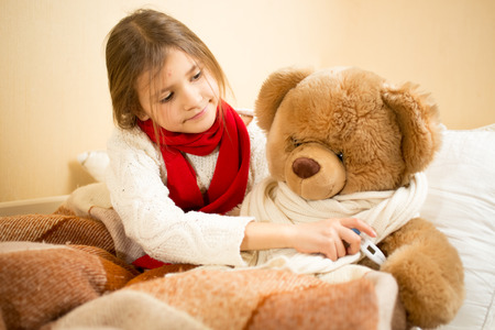 Little girl lying in bed and measuring teddy bears temperature with thermometer