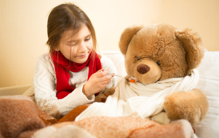 Little cute girl playing in hospital with teddy bear photo