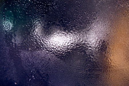 condensing: Closeup colorful texture of water condensing on glass surface Stock Photo