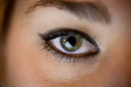 Closeup photo of female eye with computer screen reflecting in it