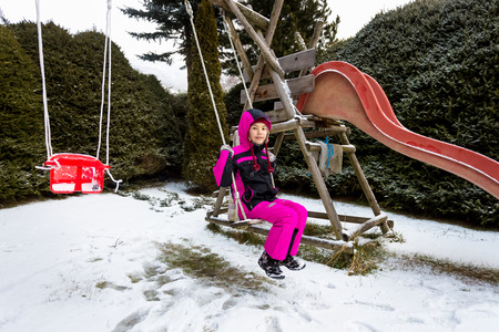 winterwear: Cute little girl swinging on playground at cold snowy day