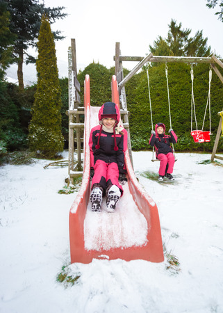Cute smiling girl riding down the slide on playground covered with snow photo