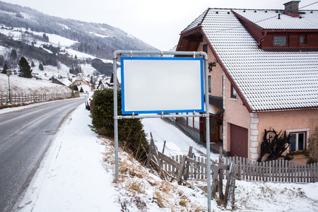 austrian village: White signpost with copy space in Austrian village at mountains Stock Photo