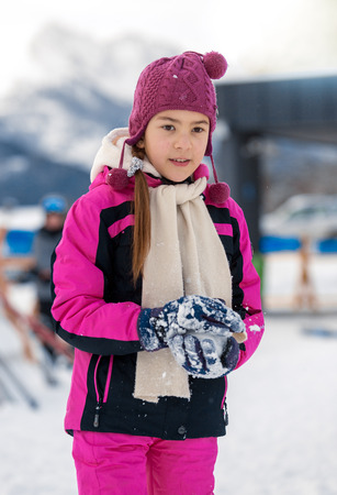 Beautiful smiling girl posing on top mountain covered by snow photo